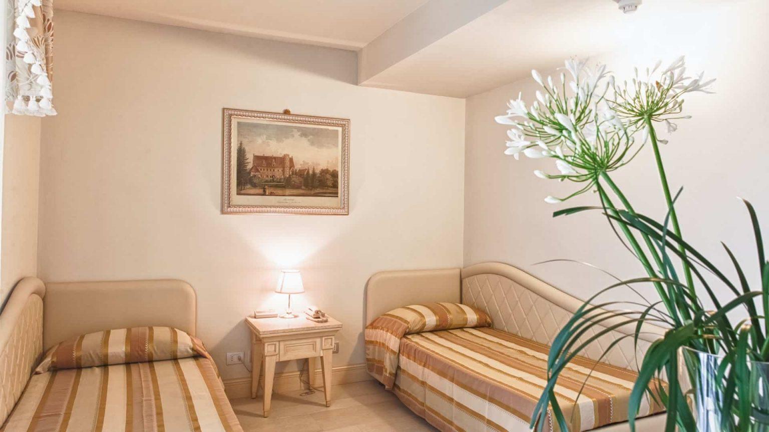 Camera family con due letti singoli e vaso di fiori
